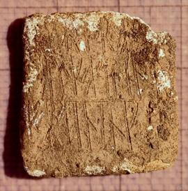 Blystykke med runer funne i ei tuft på Lurekalven.
